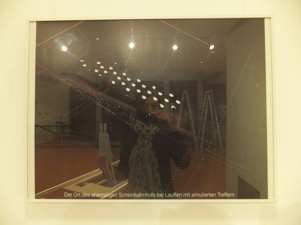 """Das Motiv der Einladungskarte: Die Scheinanlage bei Nacht, mit zeitgemäß überarbeiteter Bahnhofsattrappe. Bildunterschrift: """"Der Ort des ehemaligen Scheinbahnhofs bei Lauffen mit simulierten Treffern. """""""